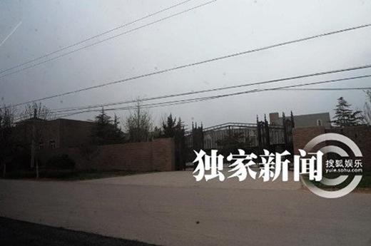 Cổng sắt với tường rào cao phía ngoài dinh thự.