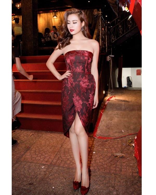 Sắc đỏ rượu được sử dụng làm điểm nhấn trên dáng váy cocktail cúp ngực của Hoàng Thùy Linh qua những mảng họa tiết hoa trải đều khắp thân váy. Phụ kiện như: hoa tai, giày cao gót được nữ ca sĩ phối hợp hài hòa với trang phục.