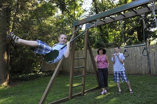 Kathleen Lanese đang chơi đánh đu với con trai Kevin, 10 tuổi, trong khi anh trai cậu bé, Brendan, 14 tuổi, đứng nhìn. Cả hai bé đều mắc bệnh tự kỉ. (Ảnh: Kathy Kmonicek)
