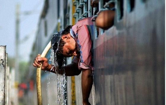 Một người đàn ông xối nước lên đầu để giải tỏa cái nóng thiêu đốt. Ảnh: PTI