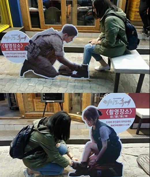 Tấm ảnh mô phỏng cảnh đại úy Yoo đang quỳ gối buộc dây giày cho bạn gái kèm theo chiếc ghế cho fan ngồi chụp ảnh. (Ảnh: Internet)