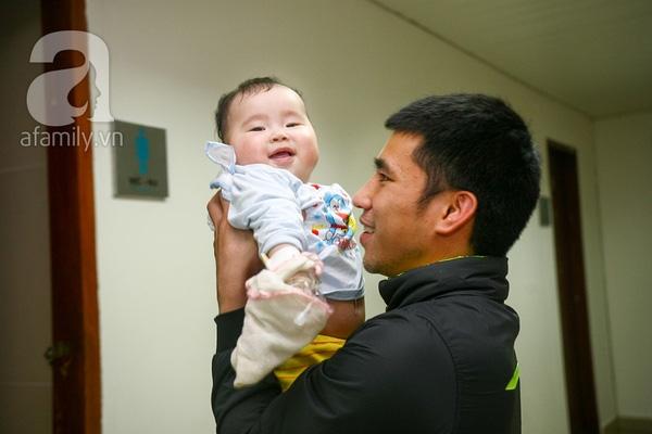 Một em bé khác, có lẽ mới vài tháng tuổi, đang chơi đùa với bố ở hành lang bệnh viện. Để tránh em tò mò, giật kim truyền trên tay ra, bố mẹ phải lấy khăn xô bọc kín lại.