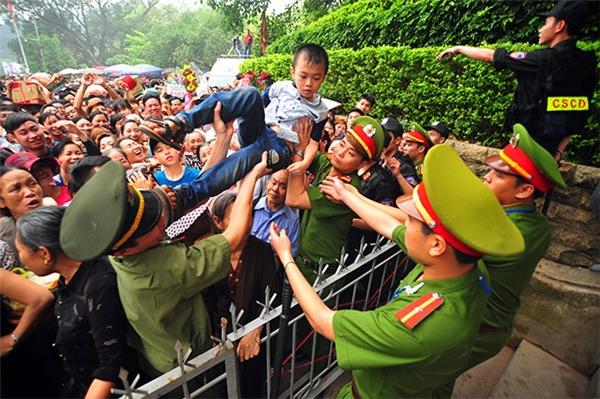 """Nhiều cha mẹ gào thét """"xin đừng xô đẩy"""" và cố gắng bế các em nhỏ qua biển người để chuyền tới tay lực lượng công an."""