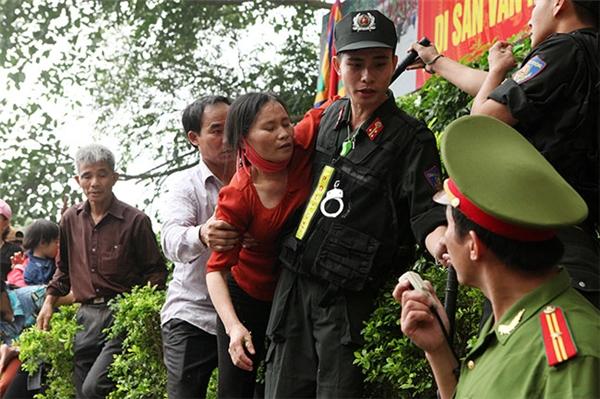 Một phụ nữ ngất lịm đi vì không chịu nổi sức chén lấn từ đám đông phía dưới.