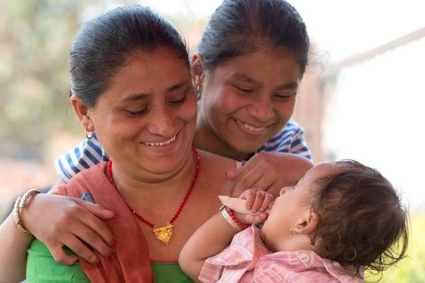 Cậu bé trong vòng tay của mẹ, cười đùa cùng chị gái.