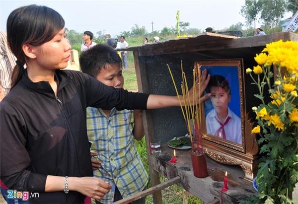 Chị Nguyễn Thị Minh Khai vuốt tay lên di ảnh trước khi giã biệt em trai Nguyễn Minh Hoàng.