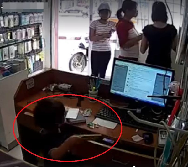 Đứa trẻ lấy trộm điện thoại từ bàn thu ngân. (Ảnh cắt từ clip)