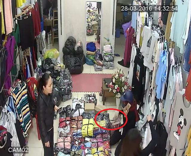 Giả vờ nghe điện thoại và móc tiền từ túi của chủ cửa hàng cho vào túi mình. (Ảnh cắt từ clip)