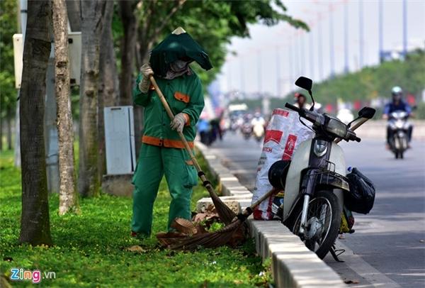 Nữ công nhân môi trường trùm thêm tấm vải trên nón để làm việc giữa trời nắng gần cầu Sài Gòn.