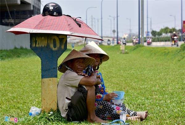 Tại khu vực gần cầu vượt Cát Lái (quận 2), vợ chồng ông Trần Văn Nông (quận 2), cùng ngồi bên cột km, che nắng bằng chiếc dù nhỏ giữa bãi cỏ đợi khách mua những chiếc khăn đa năng.