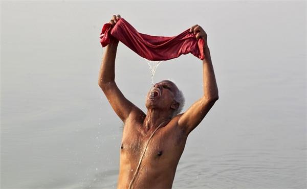 Một người đàn ông vắt tấm vải và uống nước ở sông Hằng tại thành phố Allahabad ngày 18/4. Nhiệt độ ở nơi này hôm đầu tuần ghi nhận đạt 43 độ C. Cơ quan khí tượng Ấn Độ cho biết, các mốc nhiệt độ đo được vào thời điểm này đã cao hơn từ 8 đến 10 độ so với những tháng 4 các năm trước.