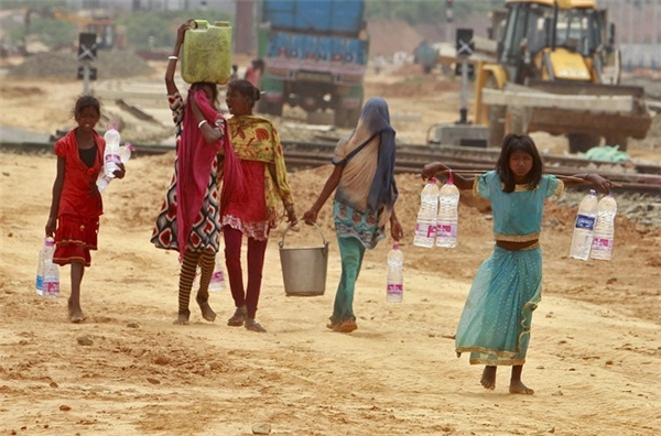 Những bé gái đi xách nước sinh hoạt ở Argatala. Chính quyền phải bố trí các xe bồn chở nước để tiếp tế cho người dân. Giới chức Ấn Độ lo ngại, đợt nắng nóng sẽ còn hoành hành nghiêm trọng trong những ngày tới. Hồi năm ngoái, hơn 2.500 người ở Ấn Độ đã thiệt mạng sau mùa hè.