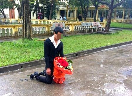 Hay tại sân trường ĐH Sân khấu Điện ảnh Hà Nội,từng có một chàng trai đứng dưới mưa cùng bó hoa trên tay để xin lỗi bạn gái. Sau nhiều giờ chờ đợi, chàng trai quỳ gục xuống. Trước cảnh tượng khổ sở của nam thanh niên, nhiều sinh viên trong trường đã đến che ô, khuyên nhủ anh ra về. Ảnh: Internet