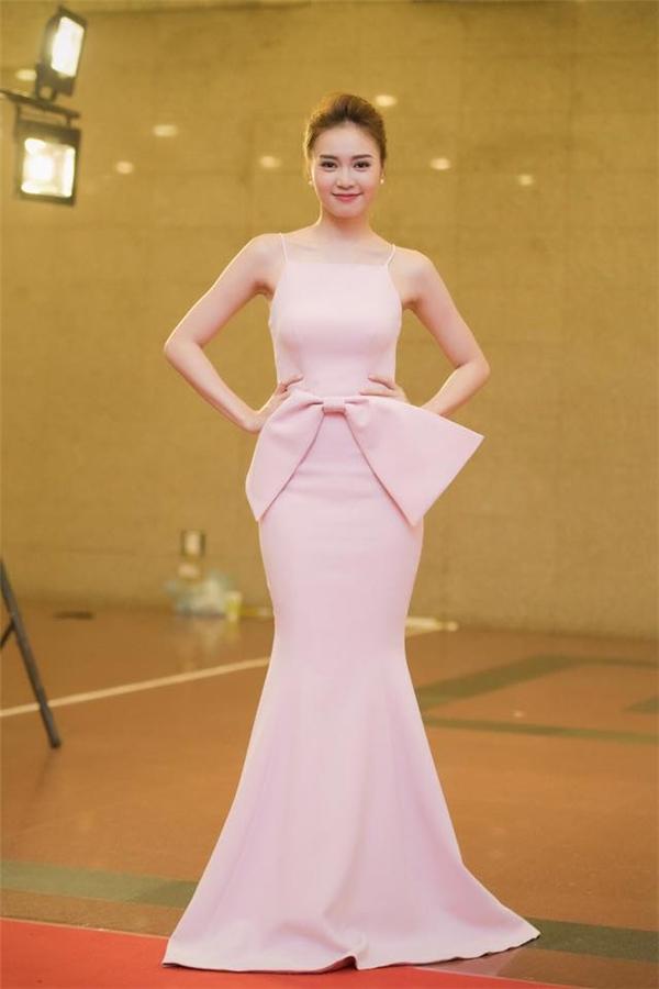 Thiết kế lấy tông hồng pastel làm chủ đạo và được tạo điểm nhấn bởi chi tiết nơ to bản. Đây là trang phục được stylist Đỗ Long đo ni đóng giày cho cô và có giá 12 triệu đồng.
