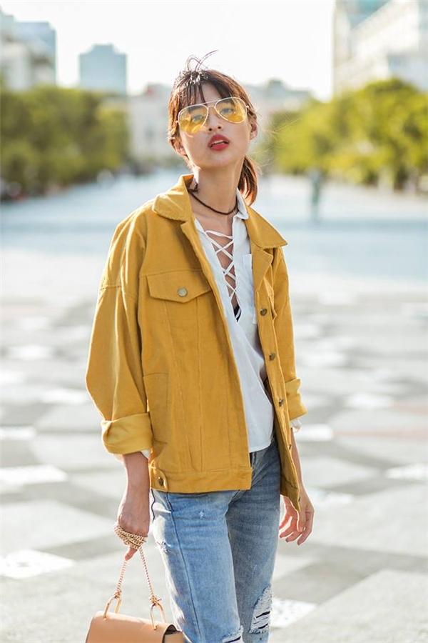 Cách phối trang phục thứ hai của cô nàng lại mang âm hưởng bụi bặm, cá tính hơn với áo khoác bomber cổ điển, sơ mi thắt dây chéo và quần jeans denim rách. Mắt kính lại là phụ kiện được Thiên Trang sử dụng làm điểm nhấn với gọng to bản cùng chất liệu trong suốt có màu.