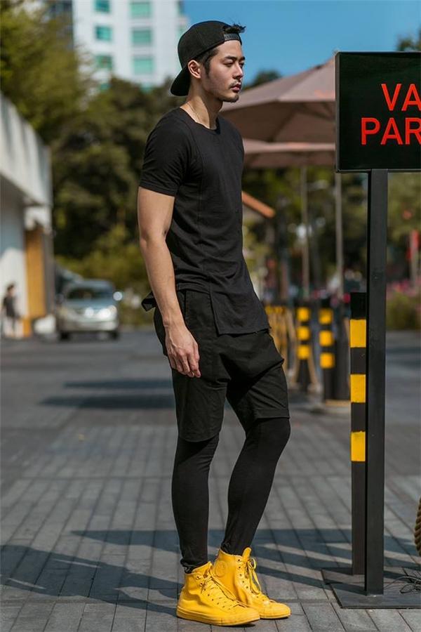 Dương Mạc Anh Quân khéo léo tạo điểm nhấn cho cả cây đen trầm mặc bằng giày thể thao màu vàng chóe không thể hòa lẫn vào đâu.