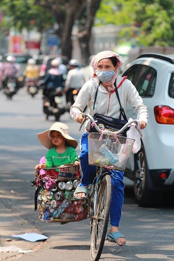 Hình ảnh một người mẹ bán ve chai đưa con đi khắp mọi nẻo đường. (Ảnh: Nguyễn Vĩnh Sơn).