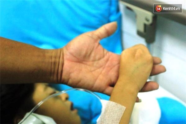 Người bố nắm lấy bàn tay bé nhỏ của con gái