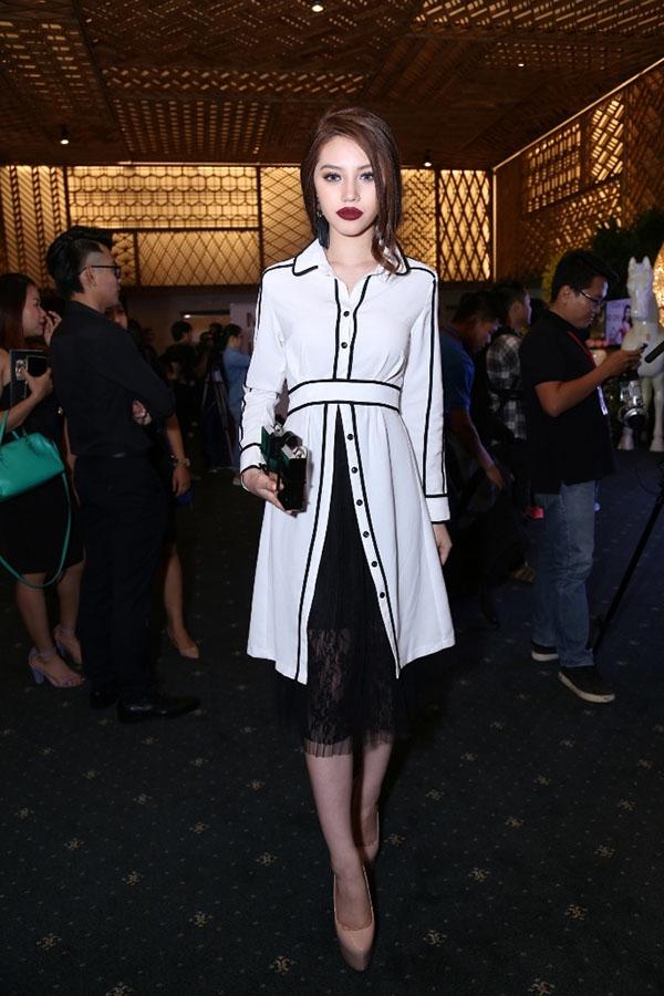 Một cô gái trẻ với bộ trang phục vừa thanh lịch nhưng không kém phần gợi cảm. Hai tông màu trắng, đen được chọn phối hài hòa, tinh tế.