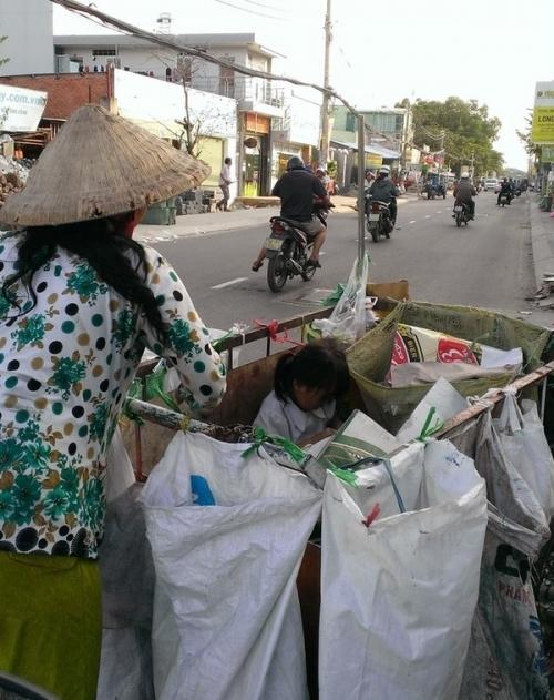 Em bé ngồi trong xe rác theo mẹ làm việc (Ảnh: Thuy Phan).