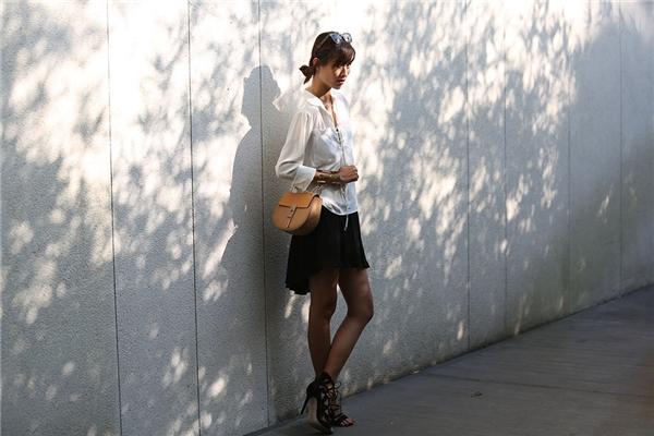 Túi đeo chéo, mắt kính gọng vuông cùng vòng tay ánh kim to bản giúp hai tông màu trắng, đen trở nên bớt đơn điệu.