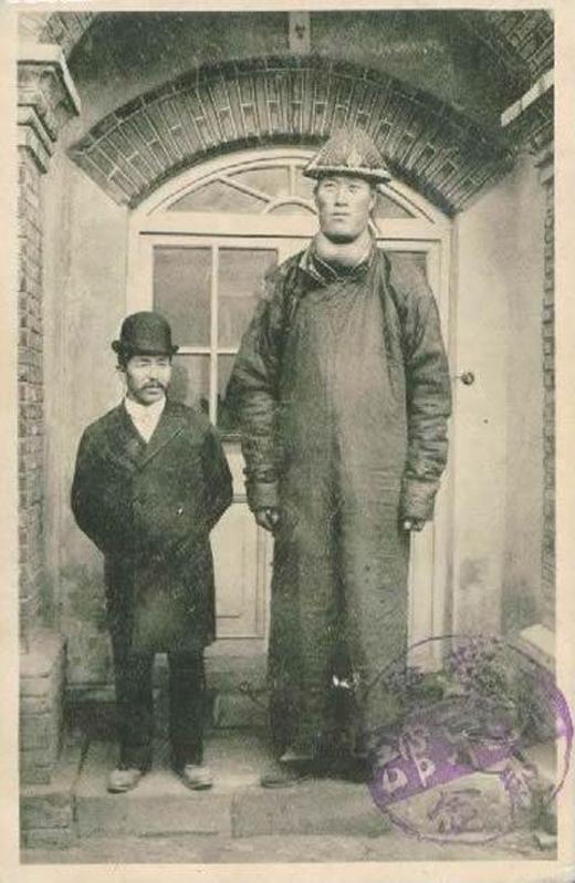 Một tấm bưu thiếp thời cuối nhà Thanh với hình ảnh một người khổng lồ Trung Quốc đứng cạnh một người đàn ông phương Tây.