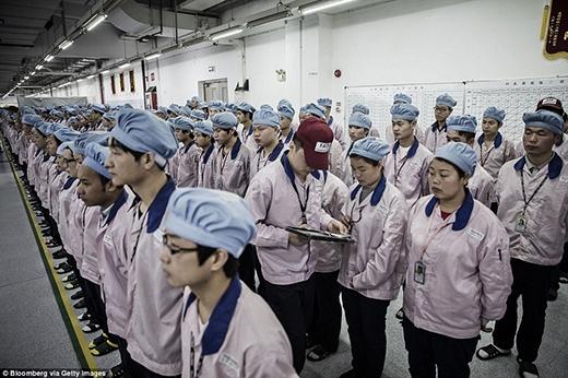 Tất cả công nhân phải đứng xếp hàng ngay ngắn trong lúc chờ quản đốc dùng iPad để kiểm tra thẻ nhân viên của mình. (Ảnh: Internet)