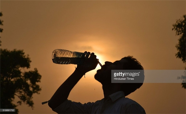 Một người đàn ông đang uống nước khi nhiệt độ lên tới 38,9 độ C ở New Delhi, Ấn Độ.