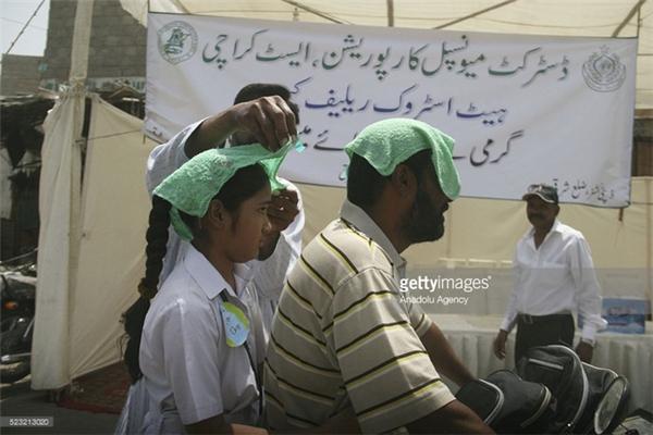 Người tham gia giao thông ở Karachi, Pakistan đội khăn ướt chống nắng.