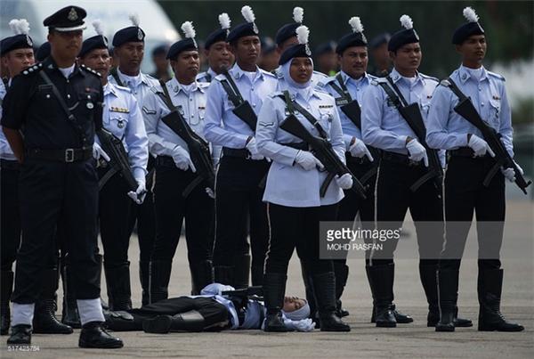 Một nữ cảnh sát cũng không đủ sức lực ngã quỵ xuống đất tại Kuala Lumpur.