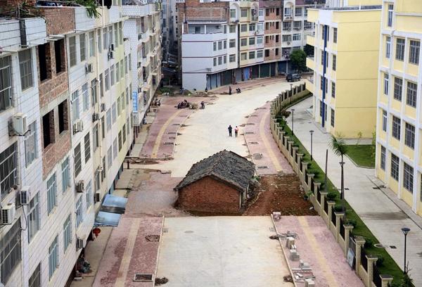 Một ngôi nhà gạch nằm lọt thỏm giữa các tòa nhà cao tầng ở Nam Ninh, thuộc Khu tự trị Dân tộc Choang Quảng Tây. Được biết chủ nhà không đạt được thỏa thuận với chính quyền địa phương về tiền bồi thường.