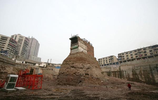 Ngôi nhà này nằm cheo lên trên một mô đất cao ngay giữa một công trường ở Trùng Khánh. Chủ nhà đã giăng biểu ngữ và treo cờ trên nóc để phản đối, không chịu bán lại đất.
