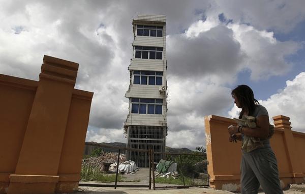 Người phụ nữ này đi ngang qua ngôi nhà 4 tầng bị dỡ bỏ một phần của mình tại Thụy An, Ôn Châu, Chiết Giang mà cô đã sống ở đây gần một năm. Do không đồng ý với khoản bồi thường, cô đã từ chối di dời dù điện và nước đã bị cắt hơn nửa năm.