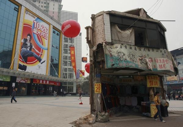 Một ngôi nhà tồi tàn nằm ngay trước một trung tâm mua sắm ở Trường Sa, Hồ Nam. Chủ nhà tận dụng địa thế thuận lợi để mở một cửa hàng quần áo.