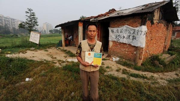 Người nông dân này cầm cuốn Luật Sở hữu đứng trước ngôi nhà của mình ở vùng ngoại ô Vũ Hán, Hồ Bắc. Ông đã tự chế ra súng thần công làm từ xe cút kít, ống tre và pháo để xua đuổi những người có ý định chiếm đất của mình.