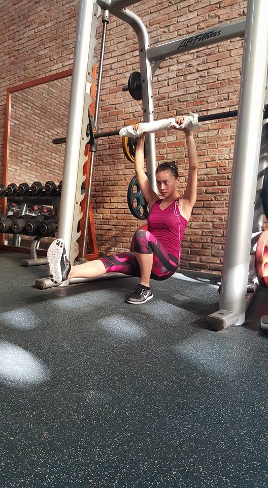 Nếu bạn cảm thấy áo bra crop-top có phần ngắn và sexy quá thì có thể chọn áo dáng dài ôm body như Ngô Thanh Vân. Người đẹp chọn một set đồ tập tông màu hồng nổi bật với áo ba lỗ, quần legging lửng và đương nhiên không thể thiếu giày thể thao.