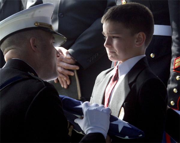 Cậu bé 8 tuổi Christian Golczynski cố gắng kìm nén nước mắt trong buổi tiễn đưa linh cữu của bố mình, một sĩ quan hy sinh trong khi đang làm nhiệm vụ.