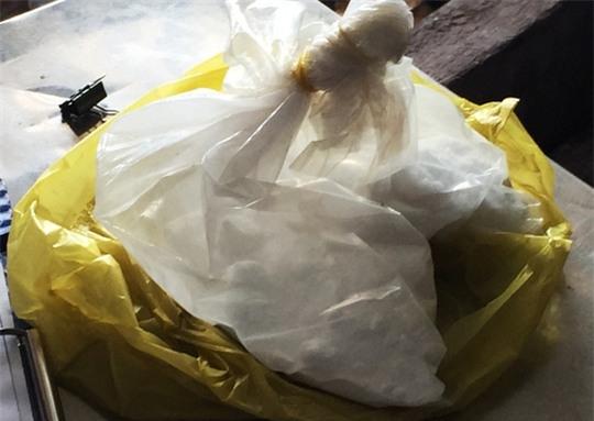 Gói bột màu trắng phát hiện tại cơ sở bán dừa của bà Lan. Theo bà, loại bột này có thể ăn mòn da tay và dùng để tẩy trắng dừa. - Ảnh: LÊ PHONG