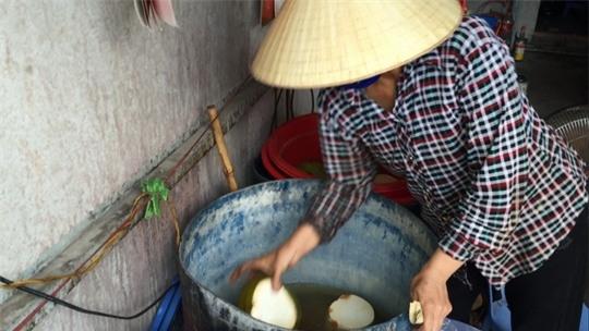 Phóng viên ghi nhận cảnh vợ ông Hồng đang lấy dừa ngâm với nước tẩy trắng bán cho khách.