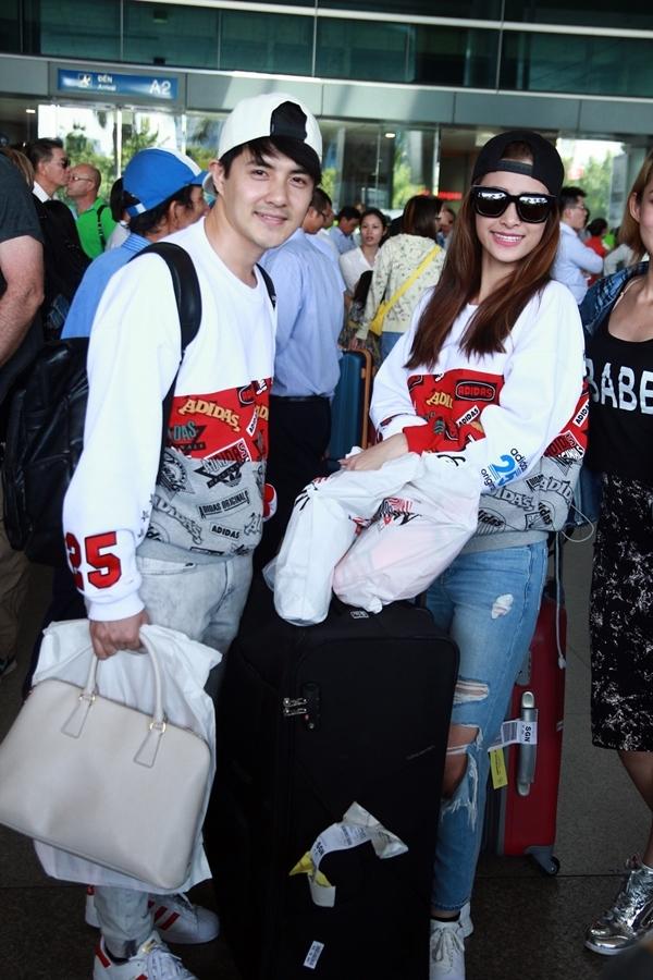 Tại sân bay, Ông Cao Thắng và cô bạn gái xinh đẹp không thể lẫn vào đâu với chiếc áo phom rộng cùng mảng họa tiết màu đỏ bắt mắt.