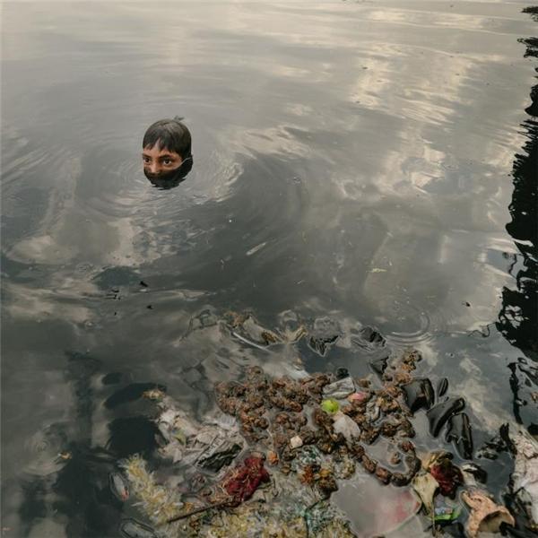 Cậu bé này đang ngụp lặn dưới làn nước đen ngòm của sông Yamuna để mò những món đồ kim loại mà người ta vứt từ trên cầu xuống, chẳng hạn đồng xu hay những bức tượng Phật nhỏ.