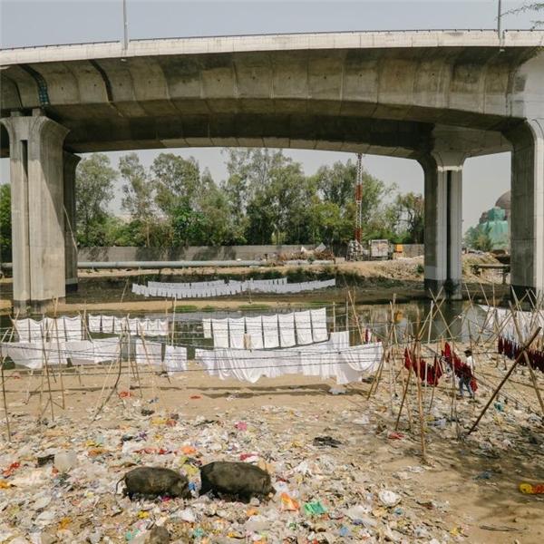 Quần áo đã được tẩy trắng đang được hong phơi bên dưới một con cầu vượt ở Delhi, ngay bên cạnh một bãi rác và một dòng kênh vẩn đục.