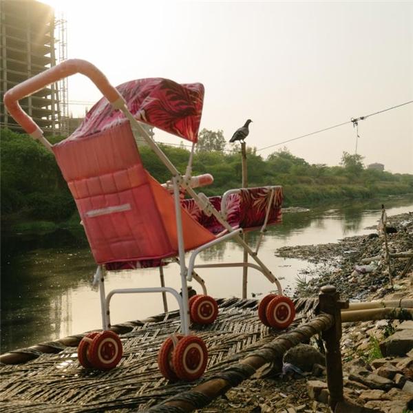Một chiếc xe đẩy vừa được giặt rửa sạch sẽ bên một bờ kênh, nơi sinh sống của rất nhiều hộ gia đình nghèo.