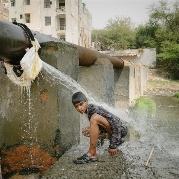 Cậu bé này tranh thủ tắm rửa bên một con kênh sau khi nhặt rác.