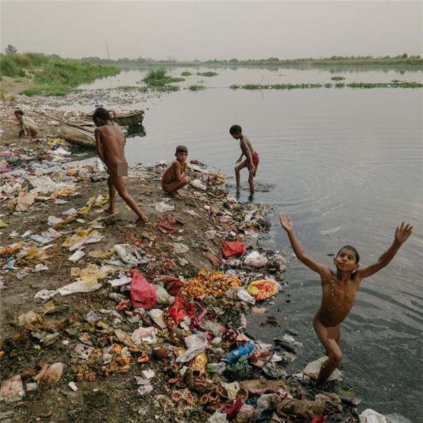 Trẻ con nhặt rác ở Delhi, trong đó có nhiều em mồ côi cả cha lẫn mẹ, thường xuyên vui chơi và tắm rửa cùng với đám rác lượn lờ xung quanh.