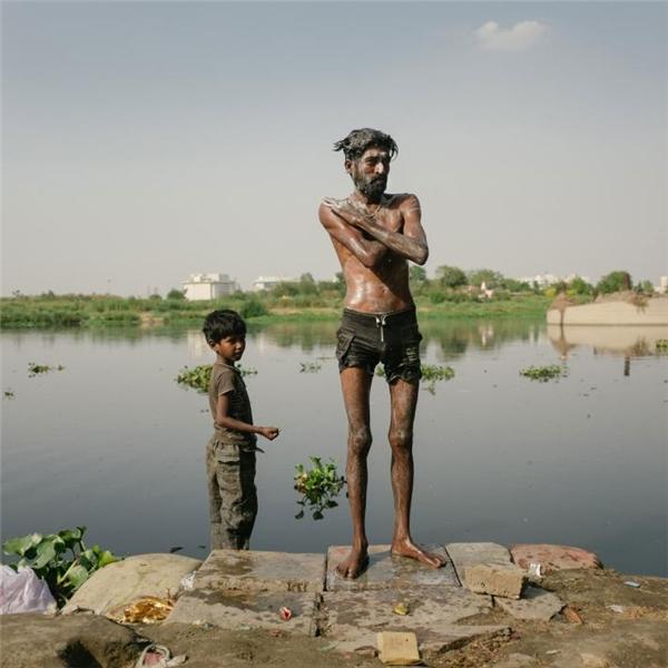 Hai bố con đang tắm ở sông Yamuna. Vì mức độ ô nhiễm quá cao nên chính quyền thành phố đã cấm tắm rửa động vật ở đây.