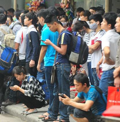 """Nhiều người cầm điện thoại """"lướt net"""" giết thời gian trong lúcchờ đợi."""