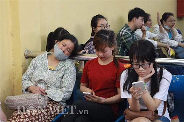 Trong lúc chờ đợi xe, một phụ nữ trung tuổitranh thủ chợp mắt cạnh hai bạn trẻ đang lướt điện thoại