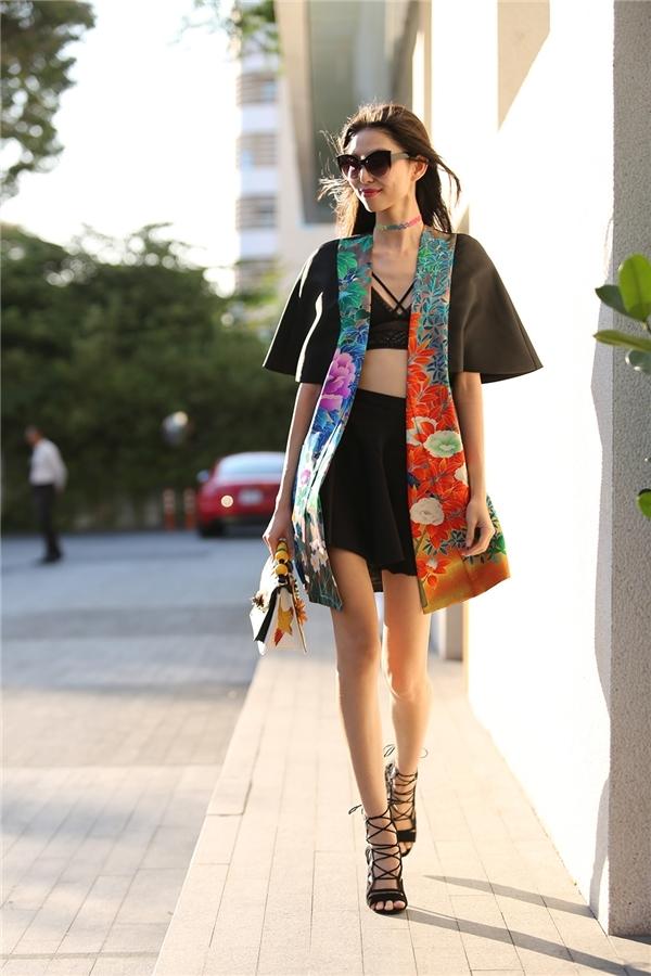Bra-top được Thùy Dương khéo léo lồng ghép vào bên trong chiếc áo khoác dáng dài kết hợp chân váy xòe điệu đà.