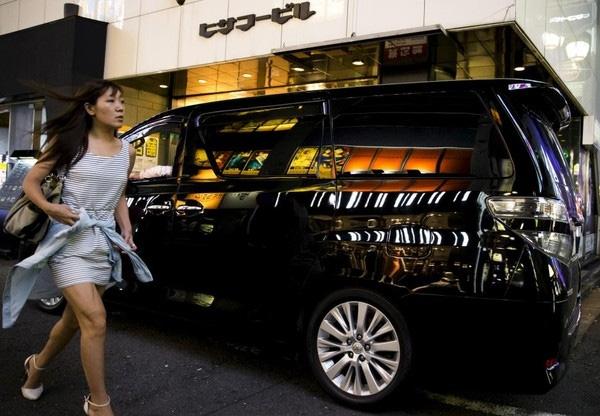 Một người phụ nữ bước đi bên chiếc xe sang trọng đỗ cạnh một hộp đêm sang trọng ở đây.